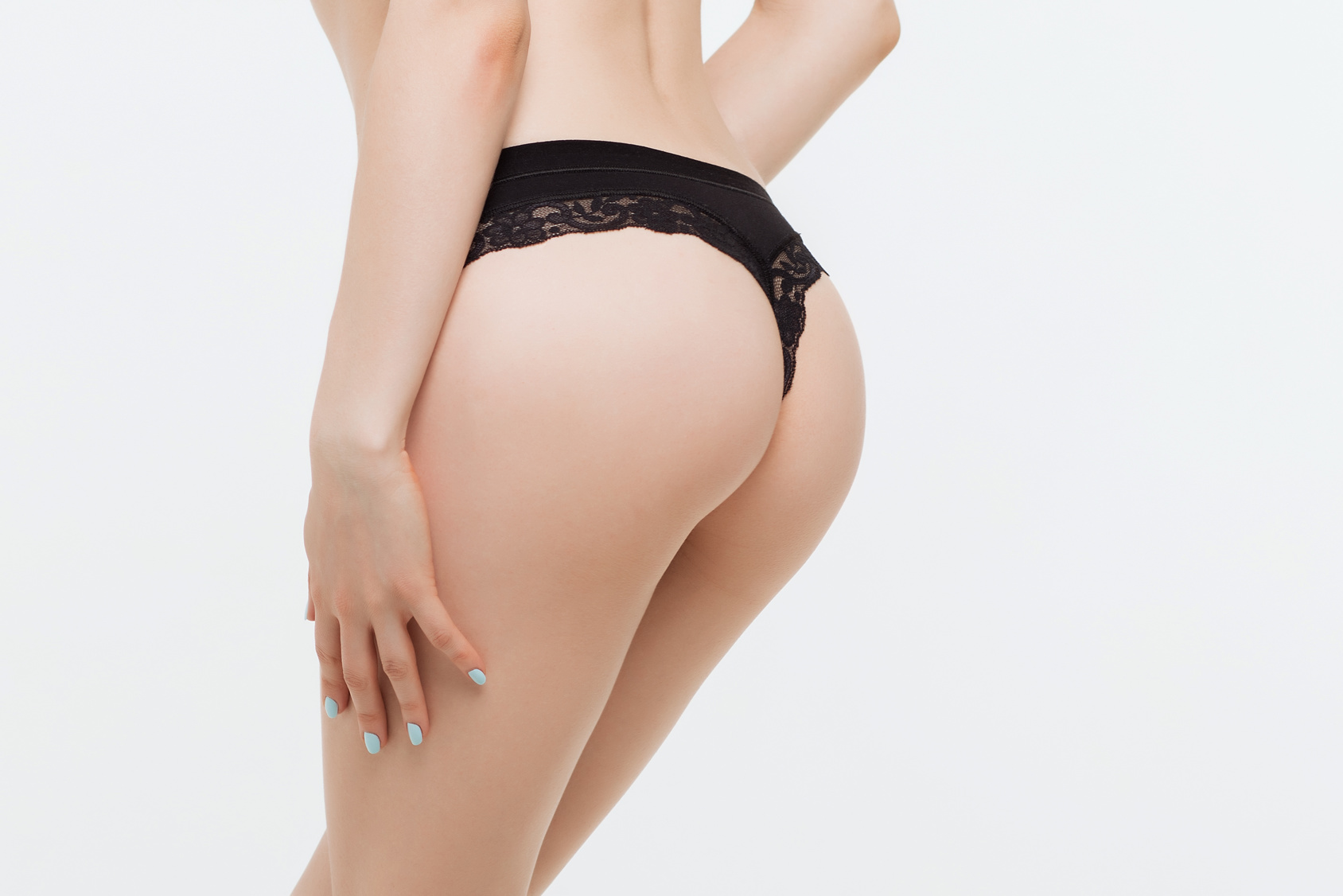 Crop side view of faceless naked female standing and keeping hands on thong